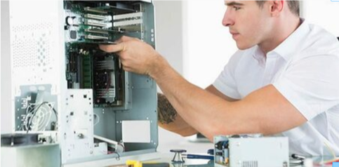 Picture of a computer technician cleaning a repairing a dismantles computer. The man is wearing a white shirt installing hardware.